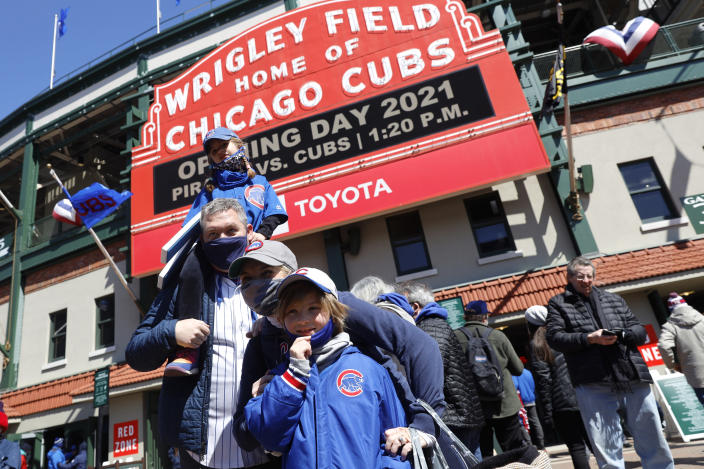 A family poses for a photo outside of Wrigley Field on the opening day baseball game between the Chicago Cubs and the Pittsburgh Pirates, Thursday, April 1, 2021, in Chicago. From New York to Seattle and everywhere in between, it is a much different opening day in 2021. Fans are back at the ballpark after they were shut out during the regular season last year because of the coronavirus pandemic. (AP Photo/Shafkat Anowar)