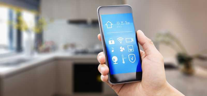 A man checks smart home devices from his smartphone.
