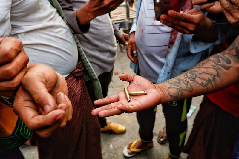 A person shows bullet shells during a protest against the military coup, in Mandalay