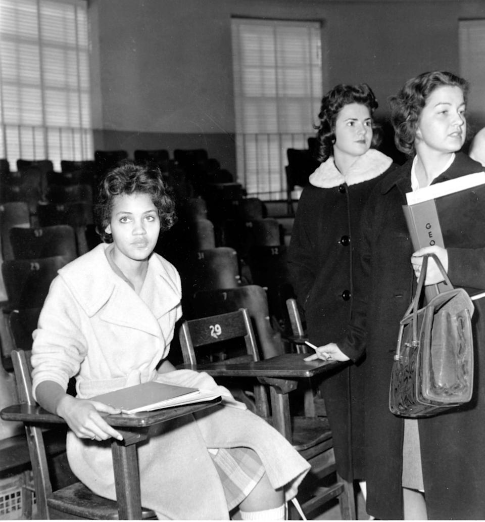 Charlayne Hunter, 18, the first Black woman to attend the University of Georgia, sits in one of her classes in Athens, Ga., on Jan. 11, 1961. The students at right are unidentified. Hunter and 19-year-old Hamilton Holmes began classes that day under court order.
