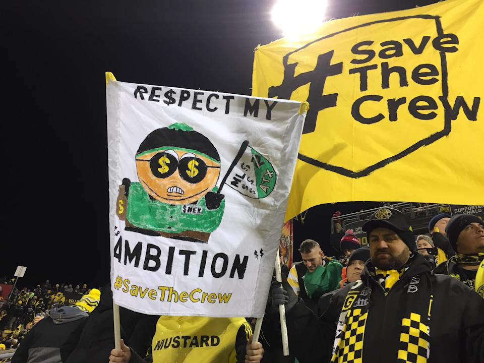 Two Columbus Crew fans hold banners during the match against NYCFC. (Henry Bushnell/Yahoo Sports)