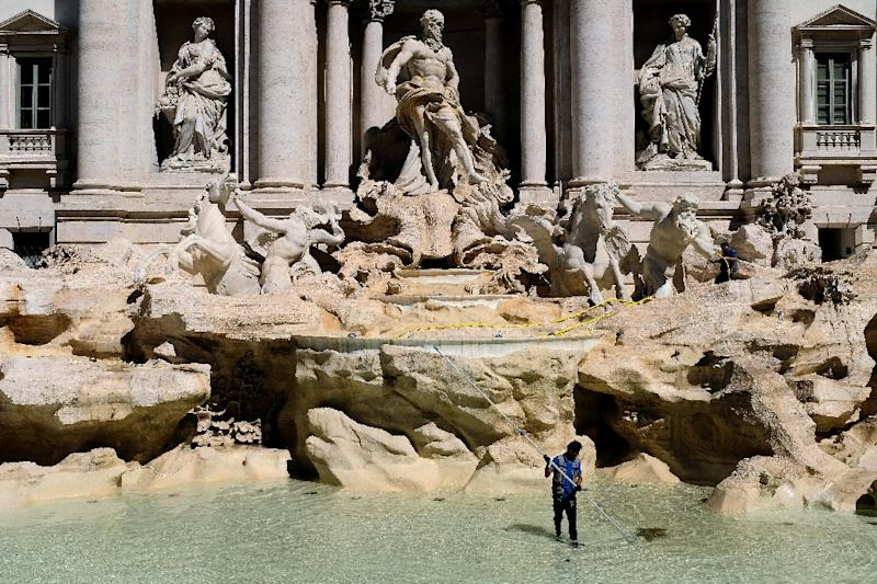 A worker collects coins tossed into the Trevi Fountain in Rome as part of a regular monthly cleaning routine. The coins which used to go to a Catholic charity will now go toward city hall projects, local media say
