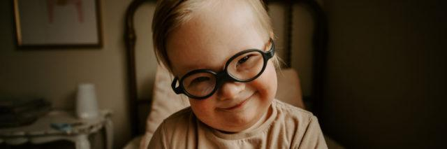 Madison's son smiling. He has Down syndrome and wears black framed eyeglasses.