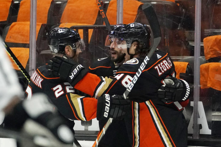 Anaheim Ducks center Adam Henrique, center, celebrates with defenseman Kevin Shattenkirk, left, and center Trevor Zegras after Henrique scored the game-winning goal during overtime in an NHL hockey game against the Los Angeles Kings Monday, March 8, 2021, in Anaheim, Calif. The Ducks won 6-5 in overtime. (AP Photo/Mark J. Terrill)