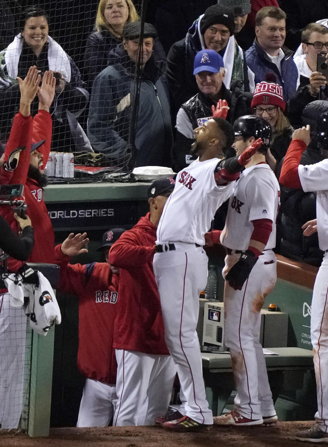 Boston Red Sox's Eduardo Nunez, center, celebrates at the dugout after hitting a three-run home run against the Los Angeles Dodgers during the seventh inning of Game 1 of the World Series baseball game Tuesday, Oct. 23, 2018, in Boston. (AP Photo/Elise Amendola)