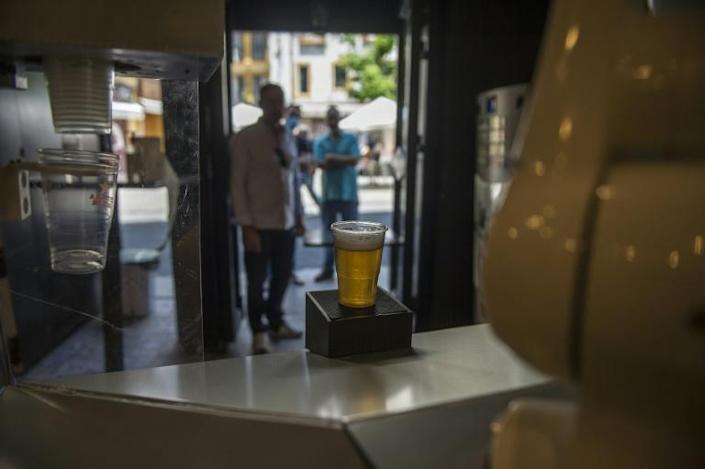 Customers queue up to be served beers poured by the Beer Cart robot, at the bar 'La Gitana Loca' (AFP Photo/CRISTINA QUICLER)