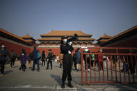 A security guard uses a loud speaker to advise tourists to scan their health code before entering Forbidden City in Beijing, Sunday, Oct. 25, 2020. With the outbreak of COVID-19 largely under control within China's borders, the routines of normal daily life have begun to return for its citizens. (AP Photo/Andy Wong)
