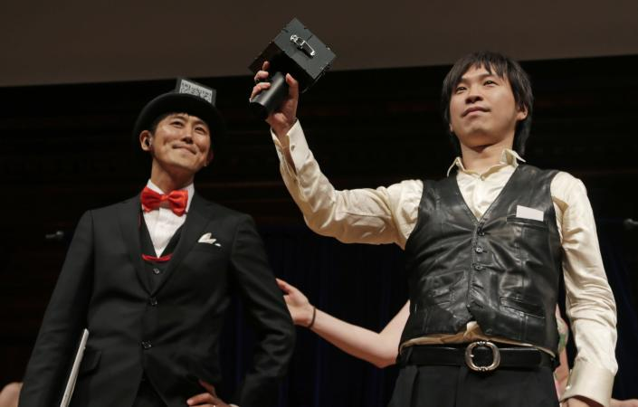 Japanese researchers Kazutaka Kurihara, left, and Koji Tsukada accept their award during a performance at the Ig Nobel Prize ceremony at Harvard University, in Cambridge, Mass., Thursday, Sept. 20, 2012. The Ig Nobel prize is an award handed out by the Annals of Improbable Research magazine for silly sounding scientific discoveries that often have surprisingly practical applications. (AP Photo/Charles Krupa)