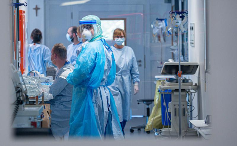 Medical staff wearing protective masks and clothing stand at the intensive care unit at the St. Josef Hospital on Wednesday in Bochum, Germany. Source: Getty