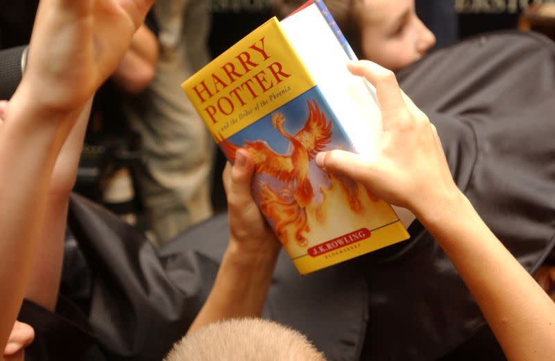 """FILE PHOTO: A child holds the latest """"Harry Potter"""" book in London"""