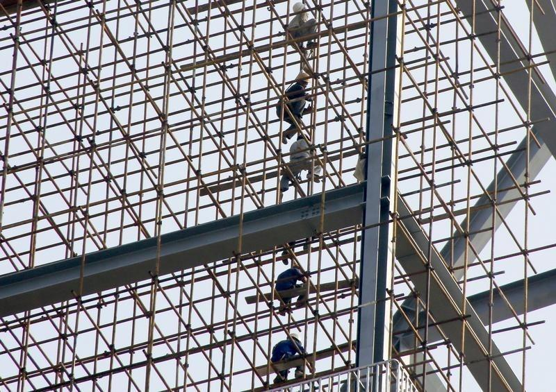 Labourers work on scaffolding of a construction site of a residential and commercial complex in Beijing