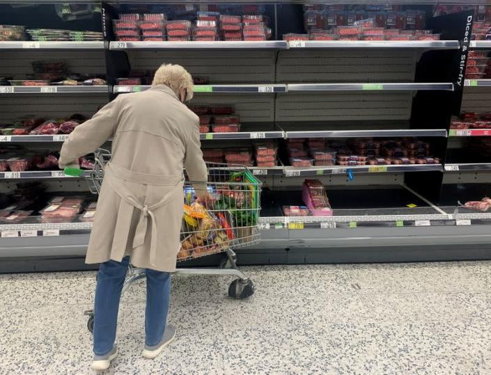 A shopper stands in front of empty shelves in the meat aisle of a supermarket in Liverpool