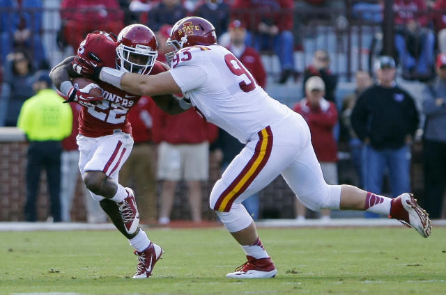 Oklahoma's Roy Finch, left, is tackled by Iowa State's Brandon Jenson, right, in the first quarter of an NCAA college football game in Norman, Okla. on Saturday, Nov. 16, 2013. (AP Photo/Alonzo Adams)