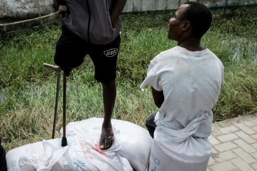 A man with one leg stands on sacks of rice printed 'China Aid,' looted from a warehouse in Beira