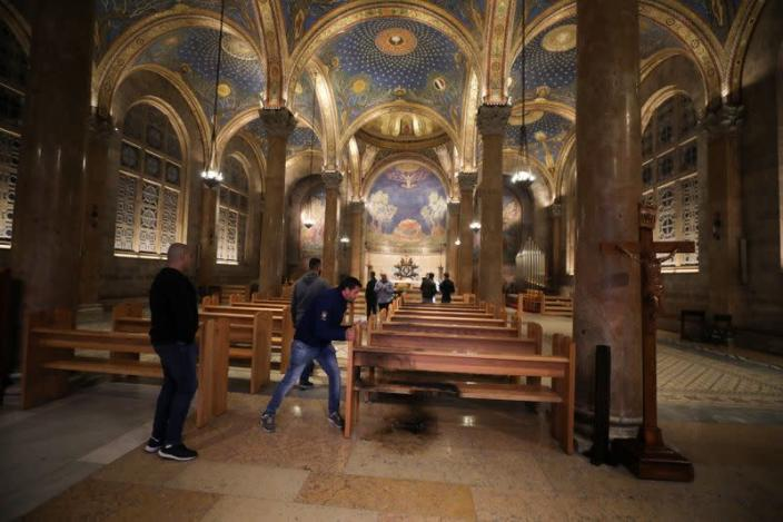 A man inspects the damaged floor after a man tried to set fire to the Church of All Nations next to the Garden of Gethsemane in Jerusalem