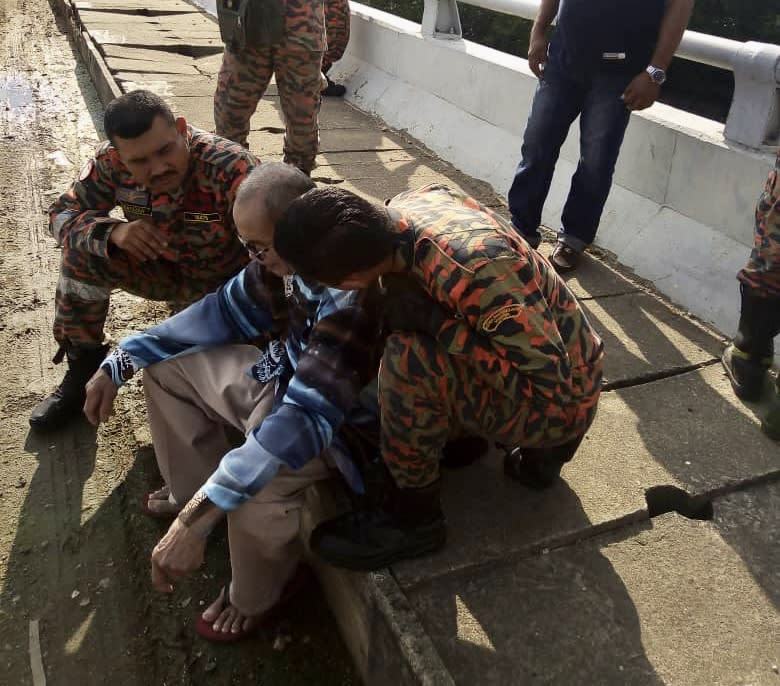 Firemen from the Pasir Gudang fire station comforting a senior citizen after he was found on the ledge of the Sungai Kim Kim bridge in Pasir Gudang today. — Picture courtesy of the Johor Fire and Rescue Department