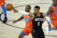 Houston Rockets' Russell Westbrook tips the ball past Oklahoma City Thunder's Chris Paul (3) during the second half of an NBA basketball first round playoff game Saturday, Aug. 29, 2020, in Lake Buena Vista, Fla. (AP Photo/Ashley Landis)