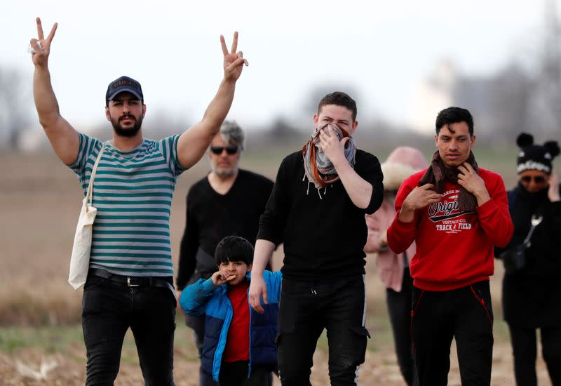 A migrant flashes V-signs as he and other migrants walk near Turkey's Pazarkule border crossing with Greece's Kastanies, in Edirne