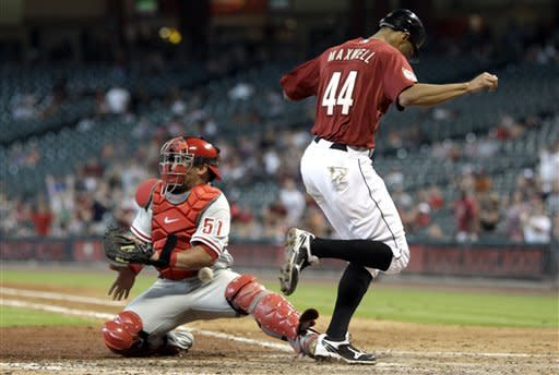 Houston Astros' Justin Maxwell (44) scores as Philadelphia Phillies catcher Carlos Ruiz loses the ball during the seventh inning of a baseball game, Sunday, Sept. 16, 2012, in Houston. (AP Photo/David J. Phillip)