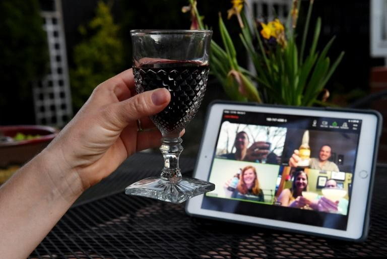 A woman lifts her glass during a virtual happy hour with friends on Zoom during the coronavirus crisis -- the video-meeting platform has soared in popularity during the pandemic (AFP Photo/Olivier DOULIERY)