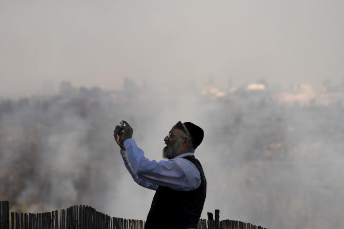 A man films wildfires burning for for the second day near Shoresh, on the outskirts of Jerusalem, Monday, Aug. 16, 2021. Israel Fire and Rescue service said in a statement that 45 firefighting teams accompanied by eight planes were working to contain five fires in the forested hills west of the city. (AP Photo/Maya Alleruzzo)
