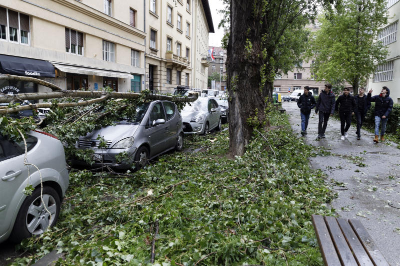 A group of students walk past cars damaged by fallen branches of a tree, in Zagreb, Croatia, Monday May 13, 2019. Stormy winds have uprooted trees, knocked over traffic lights and disrupted traffic in Croatia, injuring two people and prompting authorities on Monday to advise people to stay indoors. (AP Photo/Darko Bandic)