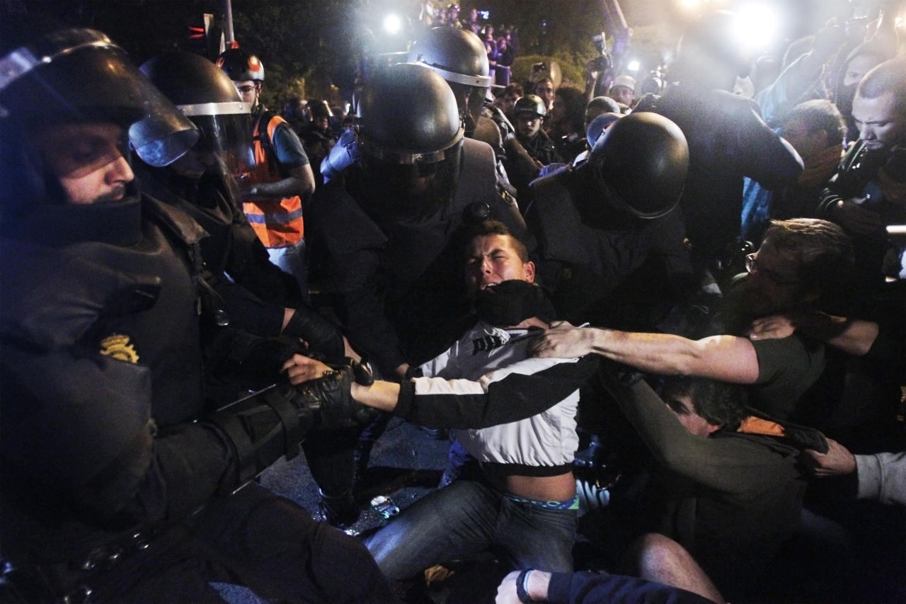 Police clash with protestors during the demonstration at the parliament against austerity measures announced by the Spanish government in Madrid, Wednesday, Sept. 26, 2012. Spain's Parliament has taken on the appearance of a heavily guarded fortress with dozens of police blocking access from every possible angle, hours ahead of a protest against the conservative government's handling of the economic crisis. (AP Photo/Andres Kudacki)