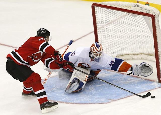 New Jersey Devils right wing Jaromir Jagr, left, of the Czech Republic, misses a shot against New York Islanders goalie Anders Nilsson, of Sweden, during a shootout in an NHL hockey game, Friday, April 11, 2014, in Newark, N.J. The Islanders won 3-2. (AP Photo/Julio Cortez)