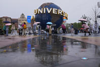 People gather and take selfies in a plaza near the entrance of the Universal Studios Beijing in Beijing, Monday, Sept. 20, 2021. Thousands of people brave the rain visit to the newest location of the global brand of theme parks which officially opens on Monday. (AP Photo/Andy Wong)