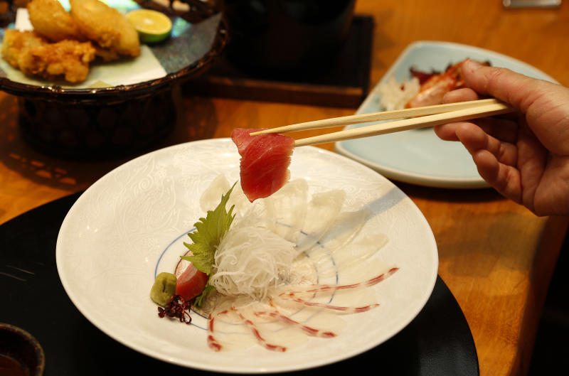 In this Wednesday, Nov. 27, 2013 photo, a slice of tuna fish is picked up from a sashimi plate of tuna, left, grouper, foreground, and Japanese blowfish at Japanese restaurant Irimoya Bettei in Tokyo. Washoku, the traditional cuisine of Japan, is being considered for designation as part of the world's priceless cultural heritage by the U.N. this week. But even as sushi and sake booms worldwide, purists say its finer points are candidates for the endangered list at home. The younger generation is increasingly eating Krispy Kreme donuts and McDonald's, not rice. (AP Photo/Shizuo Kambayashi)