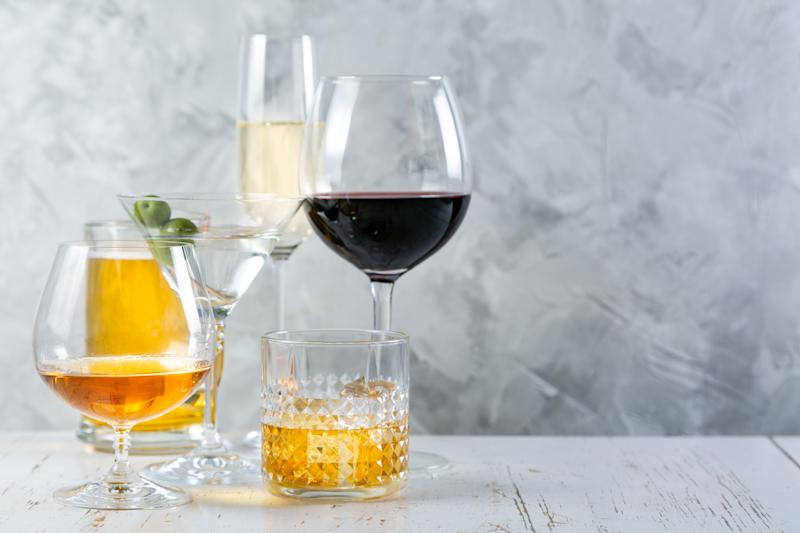 Selection of alcoholic drinks - beer, wine, martini, champagne, cognac whiskey rustic background