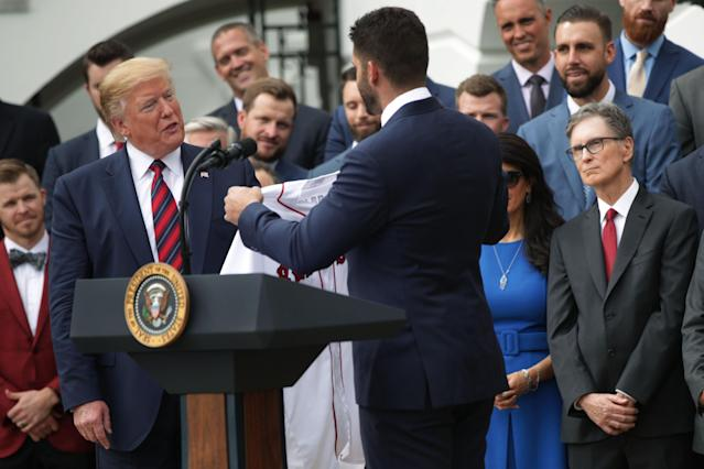 U.S. President Donald Trump is presented with a jersey by right fielder J.D. Martinez as principal owner John W. Henry look on during a South Lawn event to honor the Boston Red Sox at the White House May 9, 2019 in Washington, DC. President Donald Trump hosted the Boston Red Sox to honor their championship of the 2018 World Series.(Photo by Alex Wong/Getty Images)