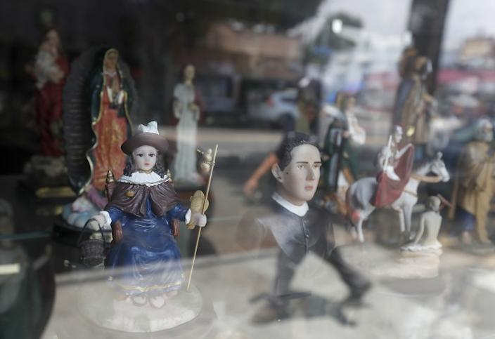 BOYLE HEIGHTS, CALIF. - JUNE 25, 2020. A figurine of Santo Nino De Atocha, left, is displayed in the window of a botanica along Cesar Chavez Boulevard in Boyle Heights on Thursday, June 25, 2020. (Luis Sinco/Los Angeles Times)