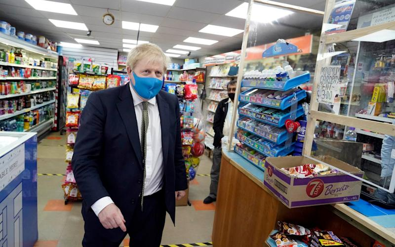 Mr Johnson was pictured in a Tory-blue mask during a constituency visit on Friday - Parsons Media