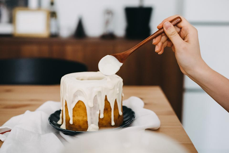 Woman's hand decorating cake with white chocolate