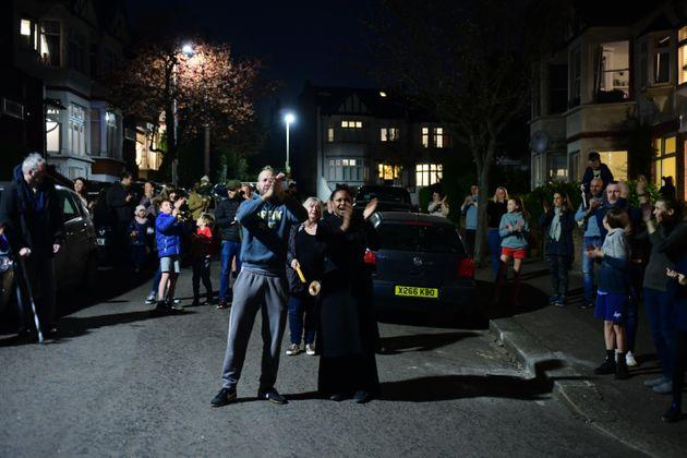 People in Woodford Green, London, join in a national applause for the NHS from their doorsteps, windows and balconies to show their appreciation for all NHS workers who are helping to fight the coronavirus.