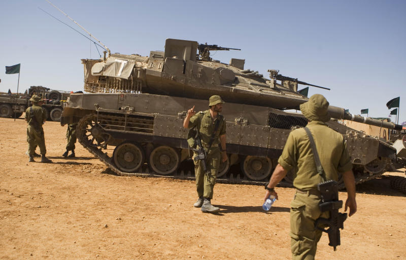 "FILE - In this Oct. 12, 2010 file photo, Israeli soldiers walk next to the tank Merkava ""Mark 4"" as they take part in a large military exercise at the Shizafon Armored Corps Training Base in the Arava desert, north of the city of Eilat, southern Israel. For more than a decade, Israel has systematically built up its military specifically for a possible strike on Iranian nuclear facilities. It has sent its air force on long-distance training missions, procured American-made ""bunker-busting"" bombs and bolstered its missile defenses. Prime Minister Benjamin Netanyahu's threats to strike Iran, voiced last week during a high-profile visit to the White House, were not empty bluster. Although a unilateral Israeli attack would probably not destroy Iran's nuclear program, it appears capable, at least for now, of inflicting a serious blow. (AP Photos/Dan Balilty, File)"