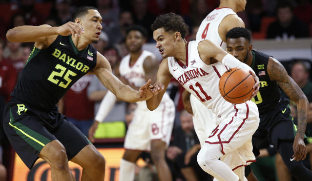 "Oklahoma guard Trae Young (11) drives between Baylor forward Tristan Clark (25) and guard <a class=""link rapid-noclick-resp"" href=""/ncaab/players/137776/"" data-ylk=""slk:Tyson Jolly"">Tyson Jolly</a>, right, during the first half of an NCAA college basketball game in Norman, Okla., Tuesday, Jan. 30, 2018. (AP Photo/Sue Ogrocki)"