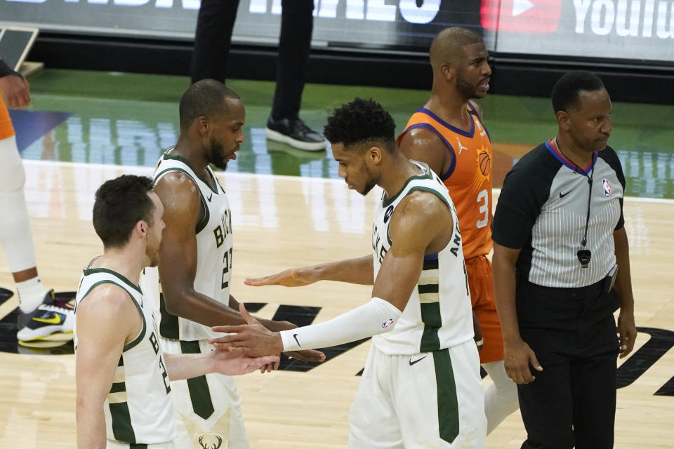 Milwaukee Bucks forward Giannis Antetokounmpo celebrates with teammates guard Pat Connaughton, left, and forward Khris Middleton, center, at the end of Game 4 against the Phoenix Suns in basketball's NBA Finals in Milwaukee, Wednesday, July 14, 2021. (AP Photo/Paul Sancya)