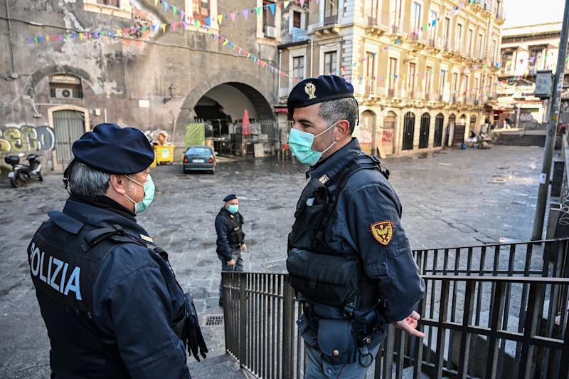 Police with the protective masks control the traditional open-air fish market closed due to the coronavirus emergency on March 12 in Catania, Italy. (Photo: Fabrizio Villa via Getty Images)