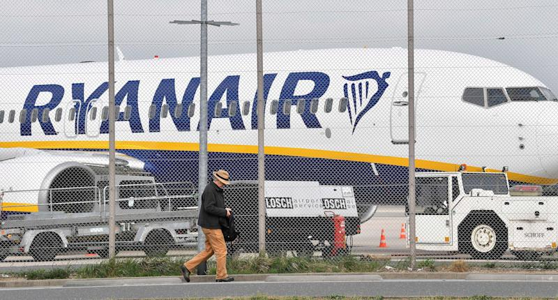 A man passes a parking Ryanair jetplane at the airport in Weeze Germany Wednesday Sept. 12 2018. Ryanair is canceling dozens of flights after pilots and flight attendants started a one-day strike over pay and conditions