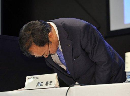 Japan's electronics company Sharp President Takashi Okuda bows his head as he leaves a press conference in Tokyo. Shares in Japanese electronics giant Sharp plunged 30 percent in Tokyo trade on Friday, a day after the company said it would cut 5,000 jobs and reported a huge quarterly loss