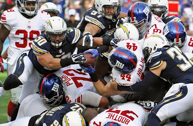 New York Giants running back Peyton Hillis carries the ball into the end zone while San Diego Chargers linebacker Manti Te'o attempts to take the ball away on a 1-yard touchdown run during the second half of an NFL football game on Sunday, Dec. 8, 2013, in San Diego. (AP Photo/Denis Poroy)