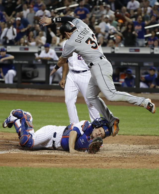 Miami Marlins' Derek Dietrich, above, is leaps over New York Mets catcher Devin Mesoraco after he is tagged out at home plate during the ninth inning of a baseball game Wednesday, May 23, 2018, in New York. The Marlins won 2-1. (AP Photo/Frank Franklin II)
