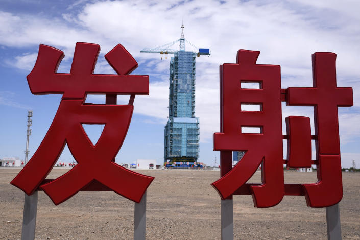 """The Shenzhou-12 spacecraft sits covered on a launch pad near Chinese characters reading """"Launch"""" at the Jiuquan Satellite Launch Center near Jiuquan, China on Wednesday, June 16, 2021. China plans to launch three astronauts onboard the Shenzhou-12 spacecraft, who will be the first crew members to live on China's new orbiting space station Tianhe, or Heavenly Harmony, from the Jiuquan Satellite Launch Center in northwest China. (AP Photo/Ng Han Guan)"""