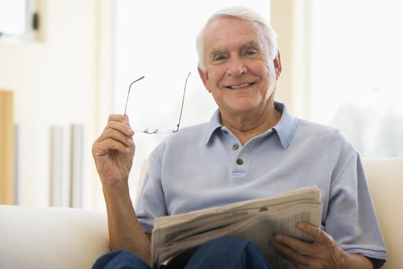 Smiling senior male holding glasses and a newspaper