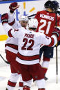 Carolina Hurricanes right wing Nino Niederreiter and defenseman Brett Pesce (22) celebrate after Niederreiter scored a goal during the second period of the team's NHL hockey game against the Florida Panthers, Thursday, April 22, 2021, in Sunrise, Fla. (AP Photo/Marta Lavandier)