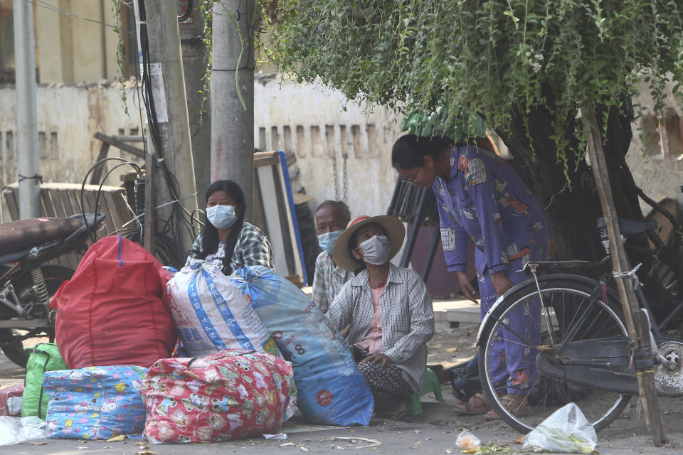 State railway employees sit with their belongings after being evicted from their home Saturday, March 20, 2021, in Mandalay, Myanmar. State railway workers in Mandalay have been threatened with eviction to force them to end their support for the Civil Disobedience Movement (CDM) against military rule. (AP Photo)