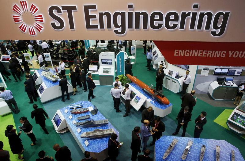 Visitors look at displays at the Singapore Technology (ST) Engineering booth during the opening day of the Singapore Airshow at Changi Exhibition Center