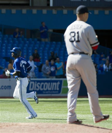 Toronto Blue Jays' Adeiny Hechavarria, left, rounds the bases past Boston Red Sox starting pitcher Jon Lester, right, after hitting a two-run home run during the seventh inning of a baseball game in Toronto on Sunday, Sept. 16, 2012. (AP Photo/The Canadian Press, Nathan Denette)